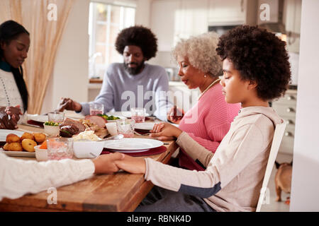 Multi generation mixed race family holding hands and saying grace before eating their Sunday dinner, side view - Stock Photo