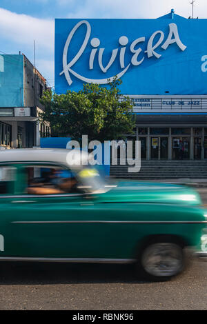 Old American car speeding past the Riviera cinema in Havana, Cuba