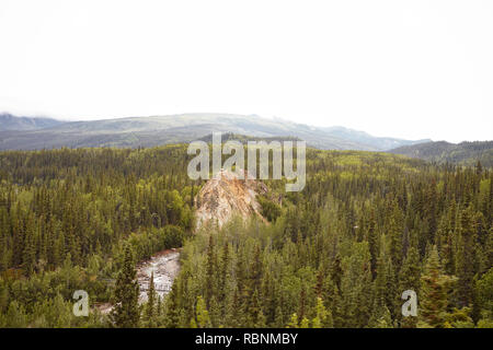 River Running Through Wooded Valley Between Mountains In Alaska - Stock Photo