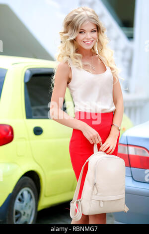 Cute girl with a backpack in the hands of looks in the camera - Stock Photo