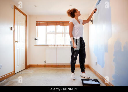Woman Decorating Room In New Home Painting Wall - Stock Photo