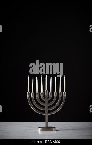 Metal Hanukkah Menorah With Unlit Candles On Marble Surface Against Black Studio Background - Stock Photo