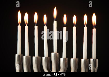 Lit Candles On Metal Hanukkah Menorah Against Black Studio Background - Stock Photo