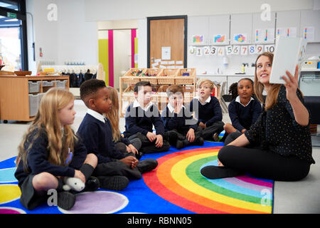 Female teacher holding up a book in front of her class of elementary school kids sitting on the floor in a classroom, side view - Stock Photo
