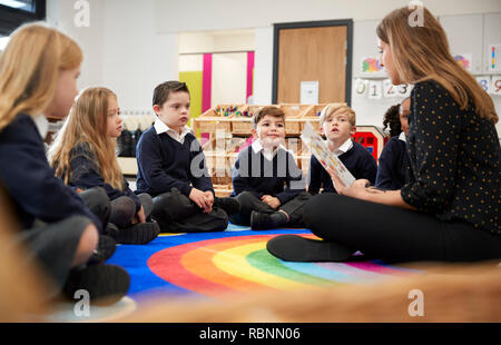 Female primary school teacher sitting on the floor in a classroom reading a book to her class, selective focus - Stock Photo
