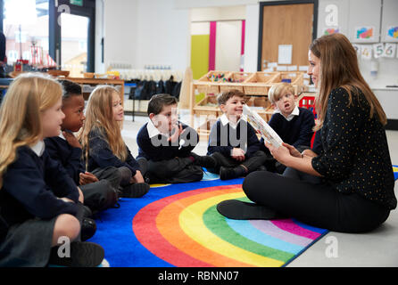Primary school kids sitting on the floor in class listening to their female teacher reading a book to them, side view - Stock Photo