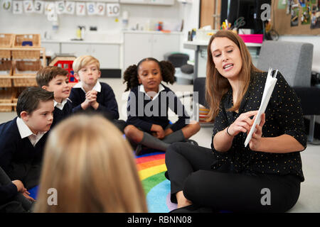 Young female primary school teacher reading a book to children sitting on the floor in a classroom, selective focus - Stock Photo