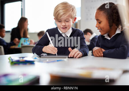 A girl and a boy using a tablet computer and stylus in a primary school class, front view, selective focus - Stock Photo