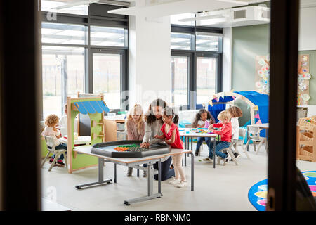 Kids playing games with a female teacher in a classroom in an infant school, seen from doorway - Stock Photo