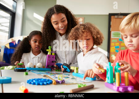 Female teacher sitting at table in play room with three kindergartne children constructing, selective focus - Stock Photo
