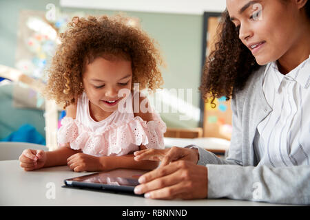Female infant school teacher using a tablet computer working one on one in a classroom with a young mixed race schoolgirl, selective focus, close up - Stock Photo