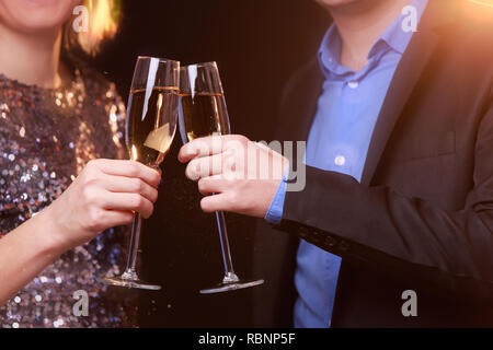 Image of woman in brilliant dress and men with wine glasses with champagne on black background - Stock Photo