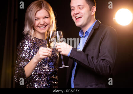 Photo of smiling woman in brilliant dress and men with wine glasses with champagne on black background - Stock Photo
