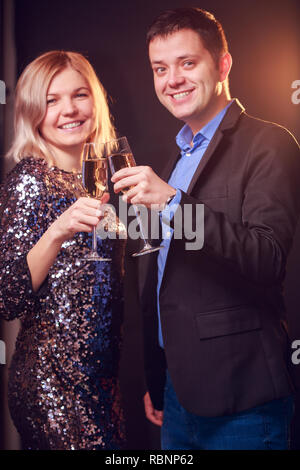 Photo of happy woman in brilliant dress and men with wine glasses with champagne on black background - Stock Photo