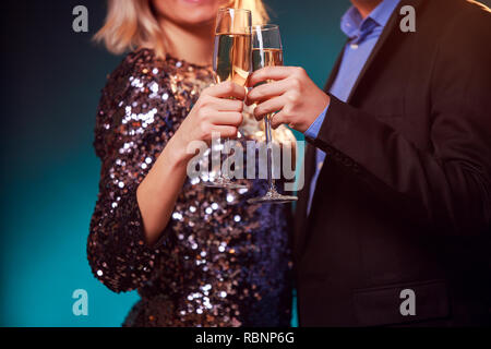 Photo of couple with champagne glasses with champagne on black background - Stock Photo