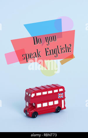 a red double-decker bus, typical of London, United Kingdom, and the question do you speak English? on a blue background - Stock Photo