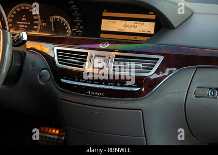 Novosibirsk, Russia - 08.01.2018: Inside the car inside a close-up of a multimedia system with the display on on the central control panel with wood a - Stock Photo