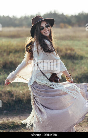 Beautiful hippie woman twirls and dancing outdoors. freedom woman spinning around - Stock Photo
