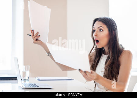 Shocked businesswoman reading paper at workplace in office. Business woman frustrated and stressed with new contract