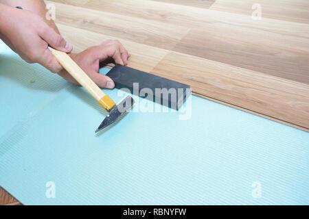 Man Installing New Laminate Wood Flooring. Worker Installing wooden laminate flooring with hammer. Handyman laying down laminate flooring boards while - Stock Photo