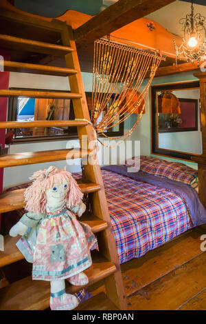 Ragdoll sitting on wooden bunkbed ladder in child's bedroom on the upstairs floor inside an old circa 1850 Canadiana cottage style home - Stock Photo