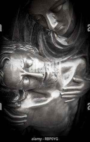 Bronze Statue of dead Jesus Christ down from the cross, being embraced by the Virgin Mary. It can be used for concepts and events. - Stock Photo