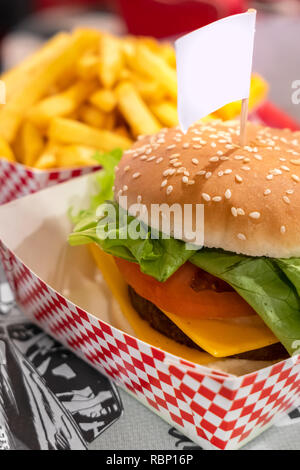 Vegetarian burger, with space for text in empty label (flag) . Vegan meat. On defocused blurry background the fries. - Stock Photo