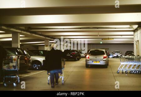 FRANKFURT, GERMANY - DEC 21, 2016: Outdoor supermarket witn senior man pushing shopping grocery cart, cars parking - Stock Photo