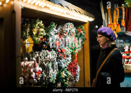Smiling fashionable woman shopping for Christmas gifts at Christmas Market in France  - Stock Photo
