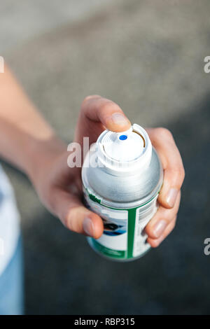 Woman hand holding high-pressure bottle can of graffiti paint or other gas as pepper security gas - Stock Photo