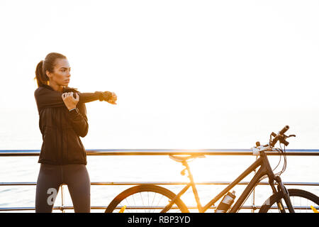 Photo of sporty woman doing stretching exercises while standing near bicycle outdoors during sunrise over ocean - Stock Photo