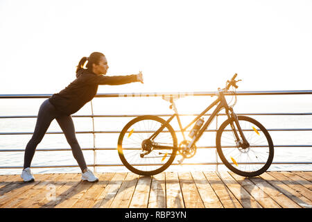 Photo of athletic woman doing stretching exercises while standing near bicycle outdoors during sunrise over ocean - Stock Photo