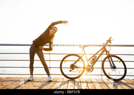 Photo of healthy woman doing stretching exercises while standing near bicycle outdoors during sunrise over ocean - Stock Photo