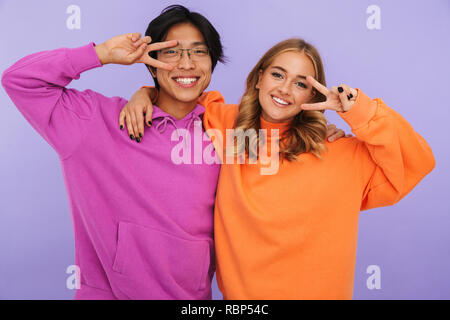 Photo of emotional young couple friends students standing isolated over white wall background showing peace gesture. - Stock Photo