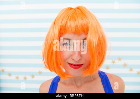 Lady red ginger wig and make up close up. Coloring and treatment professional salon service. Wig bright artificial hair looks unnatural. Hair revival procedure advice. Cosmetics for care and revival. - Stock Photo