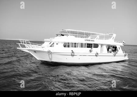 Hurghada, Egypt- February 24, 2017: Pleasure boat in sea or ocean water. Ship on sunny blue sky. Traveling on holiday cruiser. Summer vacation and recreation on sea. Water transport and vessel. - Stock Photo