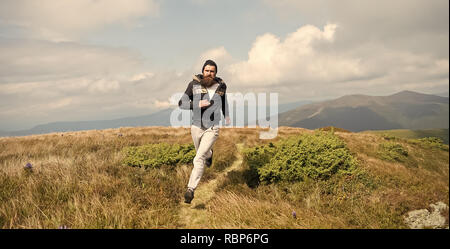 Handsome man hipster or guy runner with beard and moustache in hat run sunny outdoor on mountain top with green grass against cloudy sky on natural background. - Stock Photo