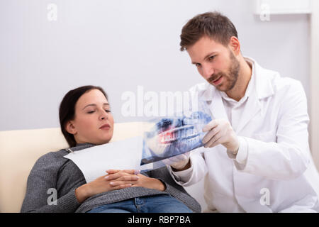 Close-up Of A Male Doctor Explaining X-ray To Female Patient In Clinic - Stock Photo
