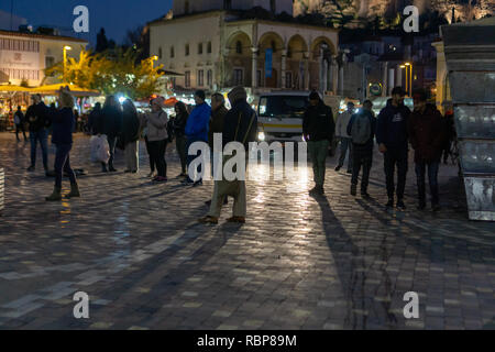 Monasteraki square was filled with happy people who enjoyed the vibrant atmosphere and amazing architecture of the area. - Stock Photo