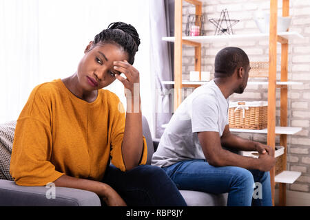 Upset Young African Couple Sitting On Sofa Ignoring Each Other - Stock Photo