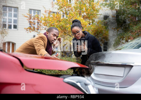 Man And Woman Looking At Smoke Coming Out From Car's Engine After Accident - Stock Photo