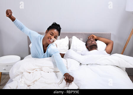 Happy African Woman Stretching While Her Husband Lying On Bed In Bedroom