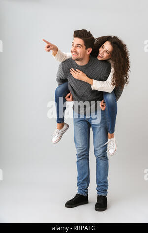 Image of young couple having fun and while man piggybacking woman isolated over gray background - Stock Photo