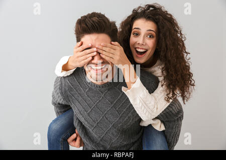 Image of excited couple having fun and while man piggybacking his girlfriend isolated over gray background - Stock Photo