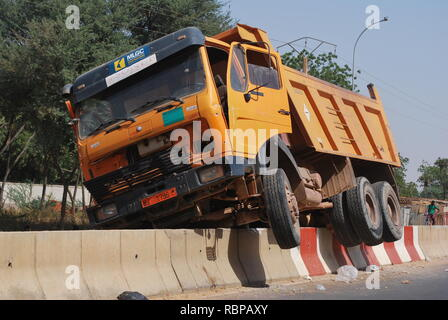 A dump truck high-centered on a cement barrier in Niamey, Niger,  Africa - Stock Photo