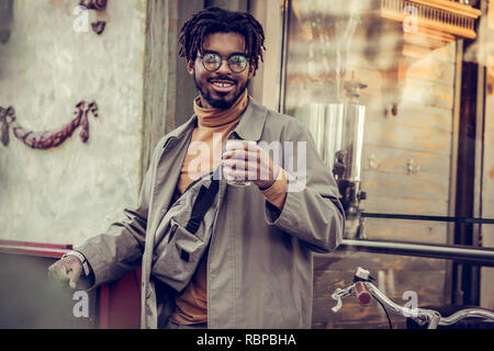 Cheerful international male person holding glass in left hand - Stock Photo