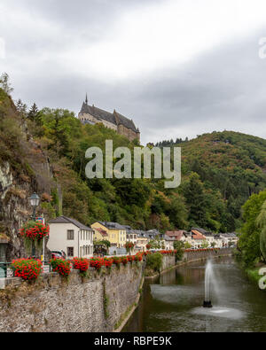 View of Vianden Castle from the Our River, perched atop a hill above the village of Vianden, Luxembourg - Stock Photo
