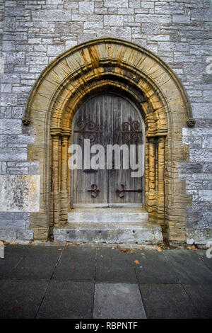 Interesting doorway found in Plymouth, England with a colorful stone frame and weathered wood and black iron door - Stock Photo
