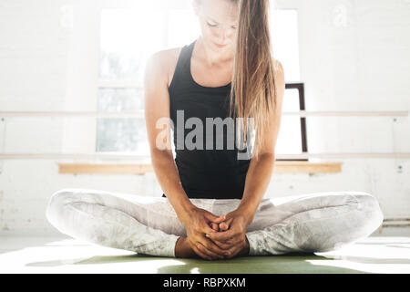 Handsome fit woman doing stretching exercise sitting on yoga mat in sunny white gum. Strong spoty girl warming up before starting workout - Stock Photo