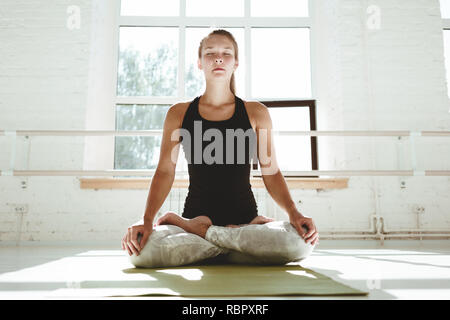 Yoga girl performs asana. Happy young woman practicing yoga in white sunny gym early morking. Horizontal - Stock Photo